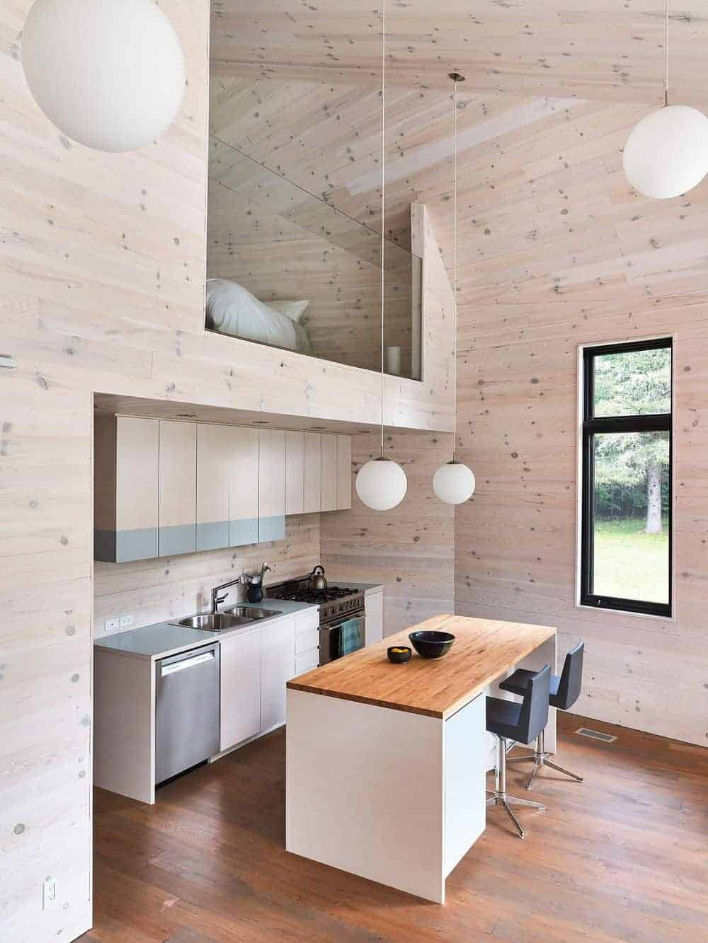 A breakfast island with black leather stools faces the light wood cabinets in this small kitchen with a glazed window and high wood plank ceiling mounted with globe pendant lights.