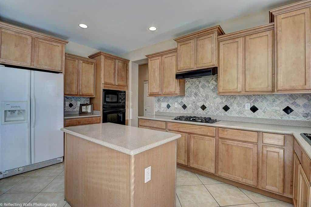 Diamond pattern backsplash adds a nice accent in this kitchen offering wooden cabinetry and a small island along with contrasting black and white appliances.