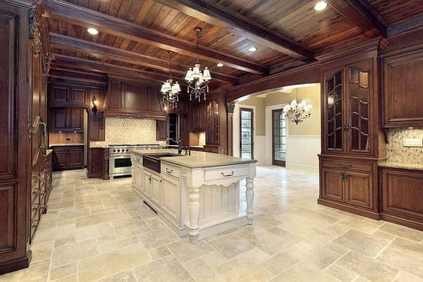 Large kitchen with wood beam ceiling, wood cabinetry, a white central island, and tile flooring.