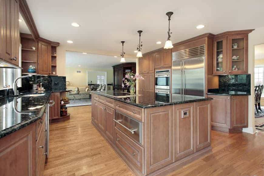 Brown kitchen boasts stainless steel appliances and wooden cabinetry matching with the island bar that's topped with a black granite counter. It is illuminated by charming pendants and recessed ceiling lights.