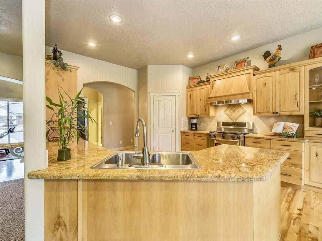 Warm kitchen with stainless steel appliances and natural wood cabinetry complementing with the hardwood flooring and peninsula that's topped with a granite counter and sink.