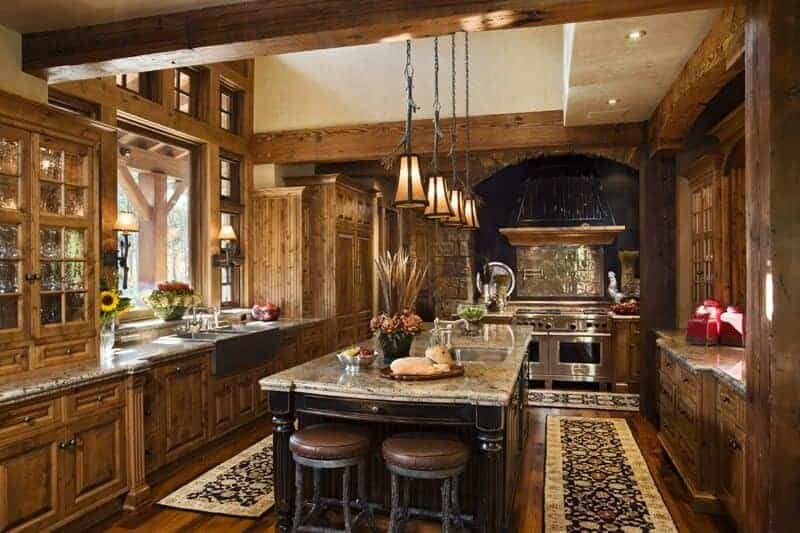 Rustic kitchen showcases an arched cooking alcove and wooden cabinetry that blends in with the hardwood flooring topped with black floral runners. There's a granite top island in the middle paired with round barstools.