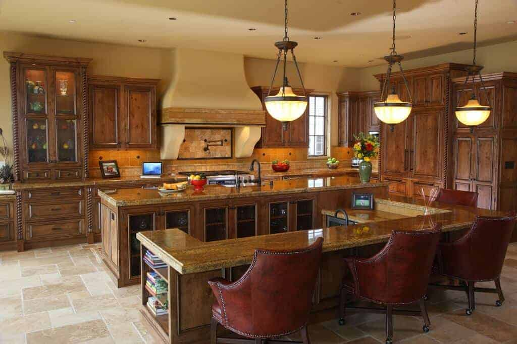 Glass pendant lights hang over the breakfast bar that's lined with brown leather chairs. It is attached to a granite top island matching with the wooden cabinetry against the yellow walls.