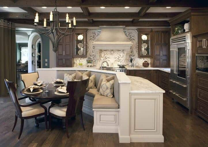 Sophisticated kitchen boasts dark wood cabinetry and a beige range hood that complements the island bar attached with a breakfast nook. It is illuminated by a candle chandelier and recessed lights mounted on the coffered ceiling.