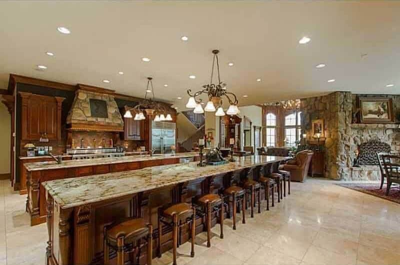 An open concept kitchen with dark wood cabinetry and two long island bars lighted by vintage chandeliers and recessed ceiling lights. It includes stainless steel appliances and a stone vent hood fixed against the black walls.