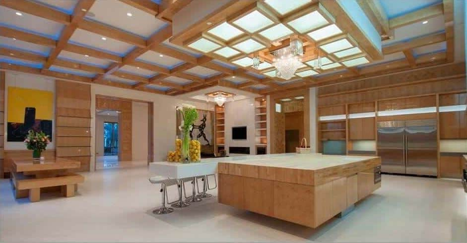 Modern kitchen illuminated by stunning light fixtures mounted on the drop ceiling that is suspended over an immense island. It is attached with a long sleek bar paired with matching stools.