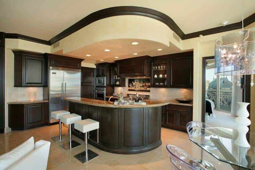 Dark wood cabinetry matches the granite top breakfast island lined with modern white barstools. There's a glass dining set on the side lighted by a crystal drum chandelier.