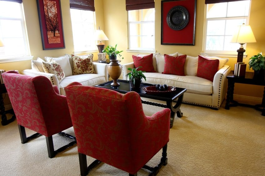Yellow living room with red accents from the wall arts, armchairs and pillows that lay on the white sofa. It has textured carpet flooring and white framed windows covered in brown roman shades.