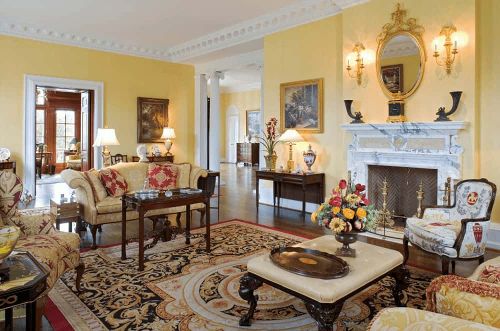 The elegant living room features classy seats and a chevron fireplace framed with white marble mantel. It includes a classic area rug and gorgeous ornate mirror mounted on the yellow wall lined with white crown molding.