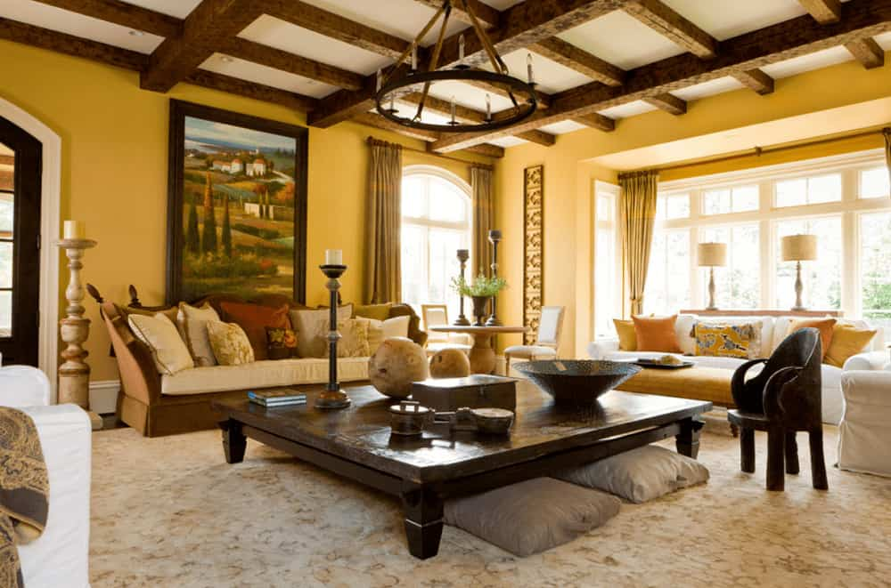 Mediterranean living room with a gorgeous landscape painting and a wrought iron chandelier that hung from the wooden coffered ceiling. It includes skirted seats and a large coffee table with gray pillows underneath.