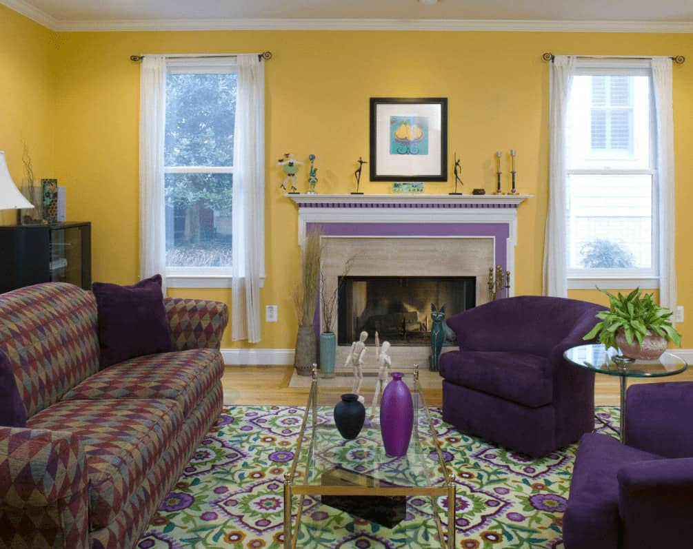Yellow round back chairs add a nice contrast to the yellow walls fitted with white framed windows. This room has a patterned sofa and glass top coffee table along with a fireplace topped with decors and a black framed artwork.