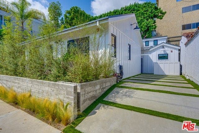 The driveway at the side of the white exterior walls has concrete blocks with carpets of grass in between to emphasize the lines. Beside this is a low concrete wall that doubles as a planter for the tall shrubs that provide privacy for the home and acts as a live fence as well.
