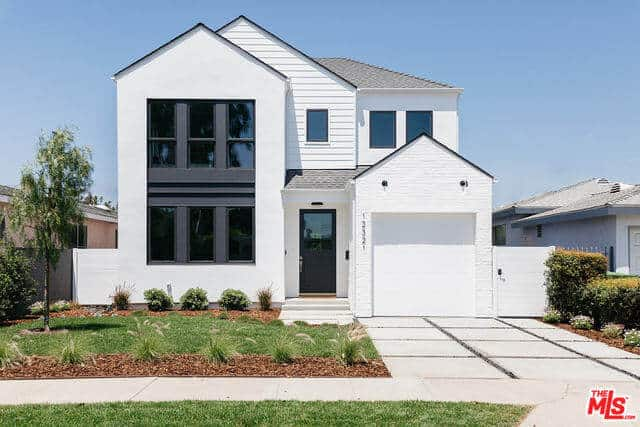 The bright white exterior walls of this home is complemented by the bleached concrete driveway leading to a stark white garage door. The brightness of these elements are somewhat counterbalanced by the front lawn that has grass and shrubs arranged in a manner that showcases the soil.