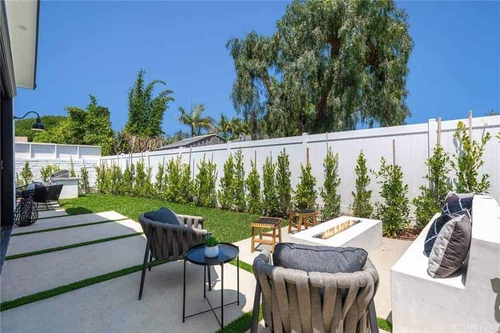 This backyard has a warm and comfortable sitting area due to its modern firepit that is inlaid with white concrete matching the stone bench. This is paired with a couple of gray outdoor chairs that stand out against the concrete flooring that leads to a small lawn of grass and end with a surrounding white concrete wall adorned with shrubs.