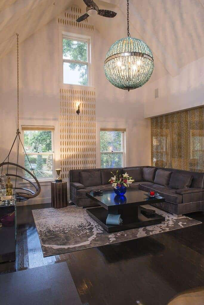 Eclectic living room with a V-shaped sofa and sleek coffee table lighted by an oversized chandelier that hung from the cathedral ceiling. It includes a spherical swing and gray area rug that lays on the dark hardwood flooring.