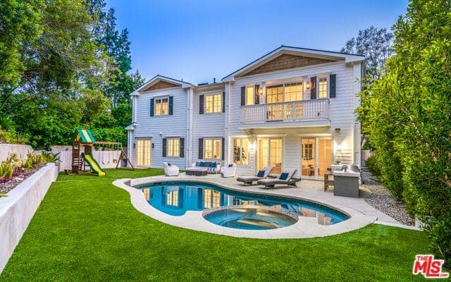 This view of the house shows a sitting area with white furniture, a couple of lawn chairs and an outdoor cooking area. These areas look down on the unique pool surrounded by a lush green lawn and a small playground for the kids on the side.