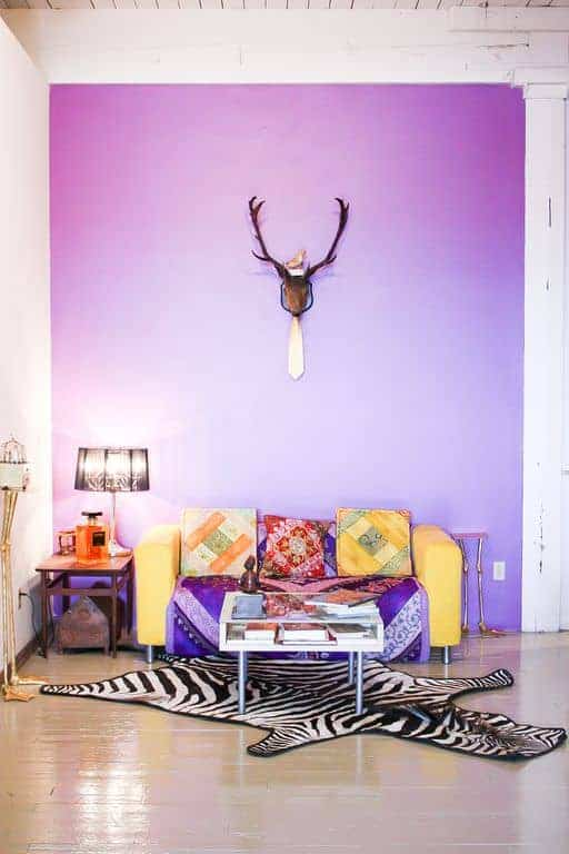 Eclectic living room with sleek coffee table and a yellow couch that adds a striking contrast to the purple accent wall mounted with a stag head decor. It includes black lampshade and zebra rug that lays on the hardwood flooring.
