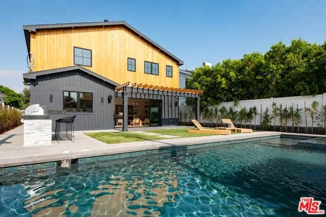 This backyard view showcases the blue pool that mirrors the brilliant blue skies. There are a couple of wooden lawn chairs to enjoy the brilliant view on the small grass lot between the pool and the house that can be accessed through a large entryway under charming trellises.