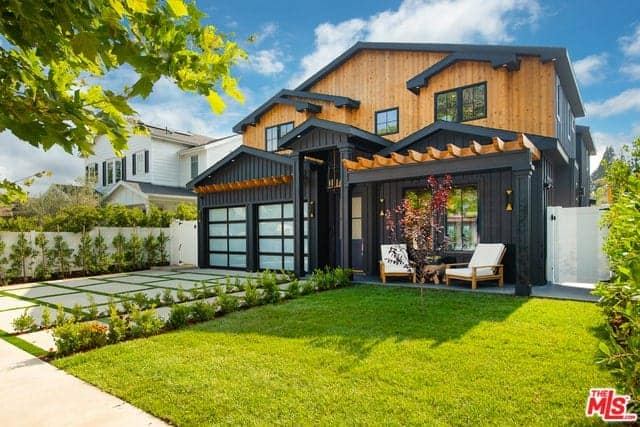 The black hue of the house exterior walls is an amazing dark background for the simple landscaping that has a driveway of concrete with green carpets of grass in between blocks. This matches well with the walkway and the lawn of grass on the far right.