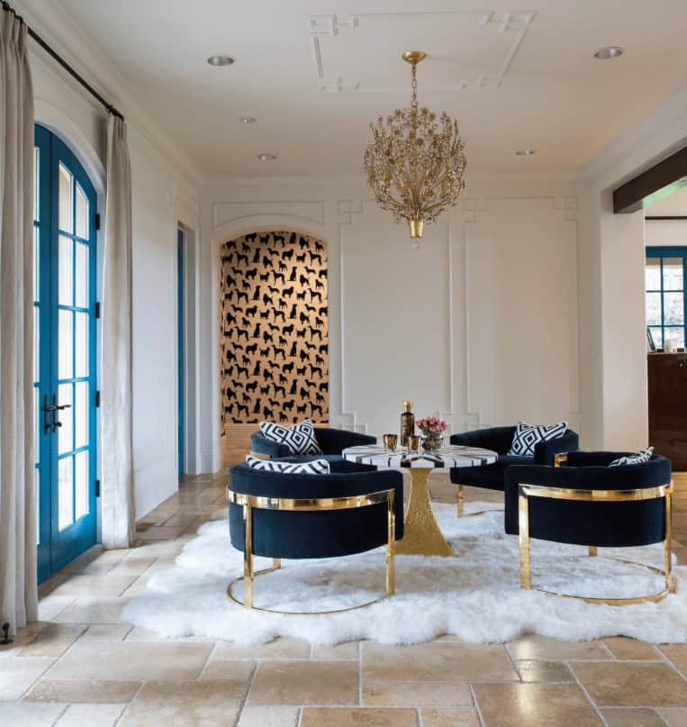 Elegant living room with classy round back chairs and a sleek coffee table lighted by a fabulous gold chandelier. It has a blue French door and limestone flooring topped by a sheepskin rug.