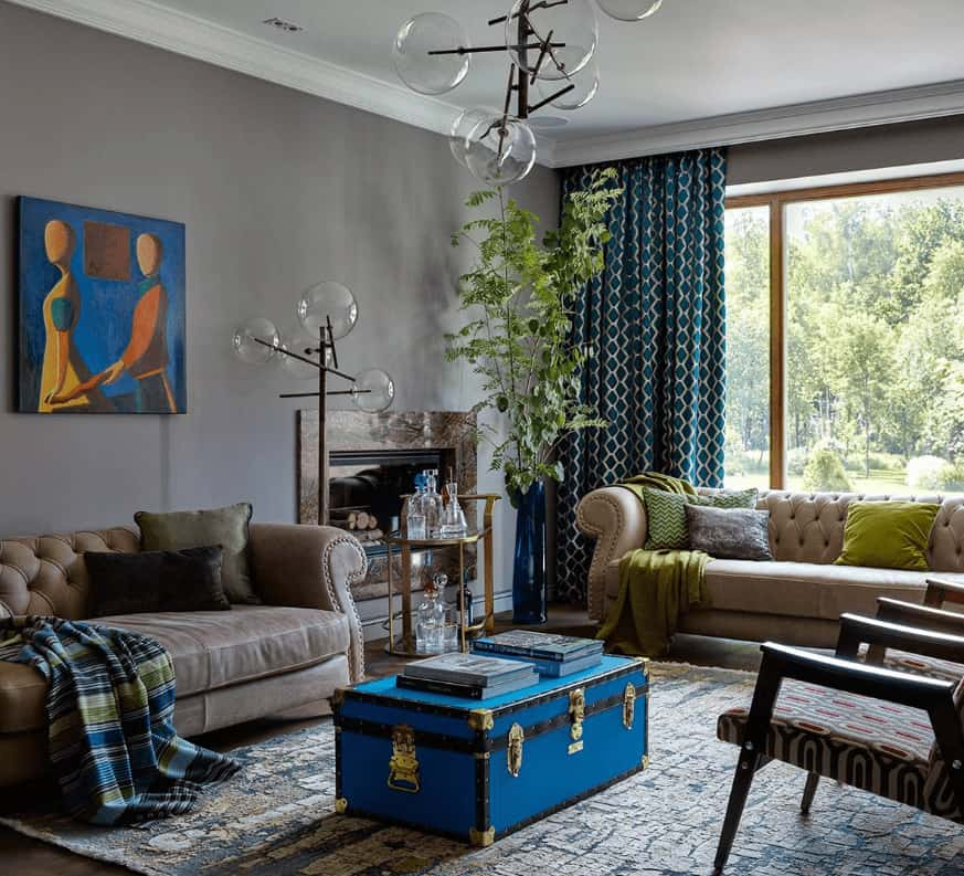 Eclectic living room illuminated by glass globe floor lamp and a matching chandelier that hung over the blue chest coffee table. It has lovely artwork and patterned drapes covering the wooden framed windows that overlook the lush greenery.
