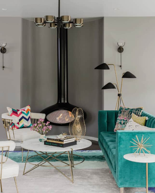 This living room boasts a green velvet sofa and white round back chairs surrounding a modern coffee table. It includes a stylish chandelier and black hanging fireplace that complements the three head floor lamp.
