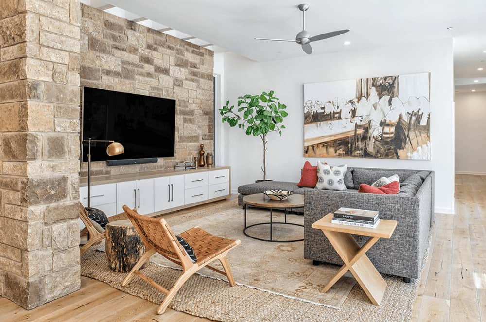 A stone brick accent wall mounted with a TV adds texture in this fresh living room with a gray sofa and wicker chairs paired with wooden tables. It includes a large artwork and brown layered rugs that lay on the wide plank flooring.