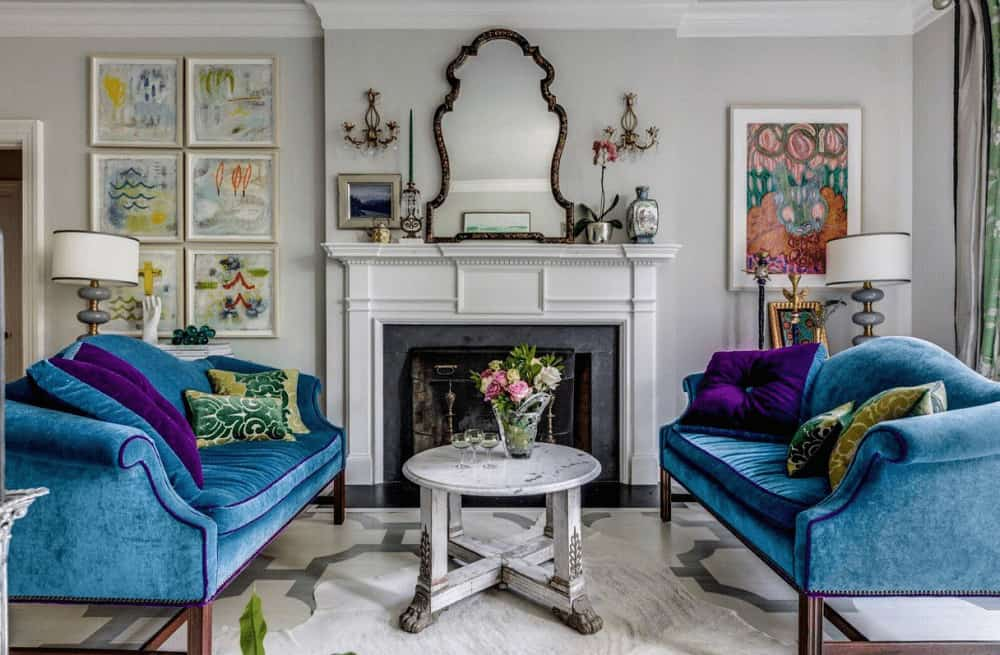 Classy living room decorated with lovely artworks and a gorgeous mirror that hung above the fireplace. It has blue velvet sofas and a round coffee table that complements the area rug.