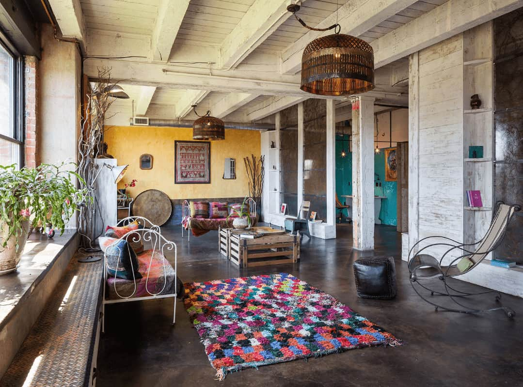 This living room boasts metal chairs, wooden coffee table and a multi-colored checkered rug that lays on the concrete flooring. It is illuminated by a pair of large dome pendants that hung from the distressed wood beam ceiling.