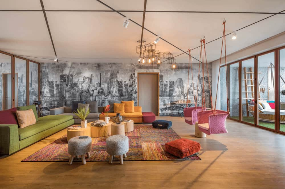 The spacious living room showcases pink hanging chairs and multi-colored sofas surrounding the wooden coffee tables over an area rug. It is illuminated by an industrial chandelier and white track lights.