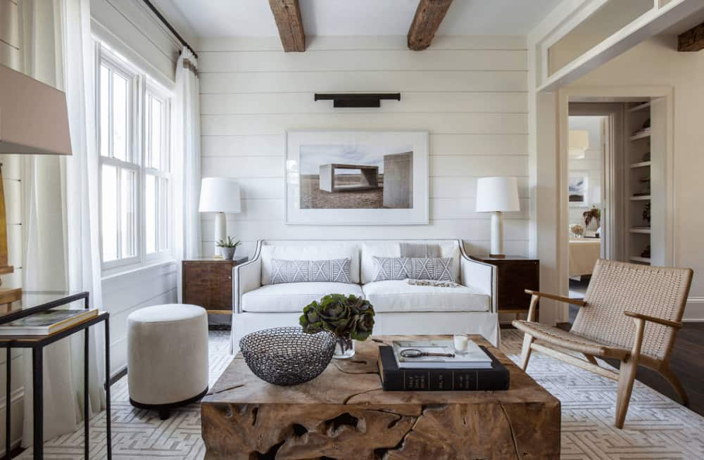 A pair of rustic wood beams complement the cube stump coffee table topped with flower vase and decorative bowl. This room has a wicker armchair and skirted sofa with a white framed photo on top mounted on the shiplap wall.