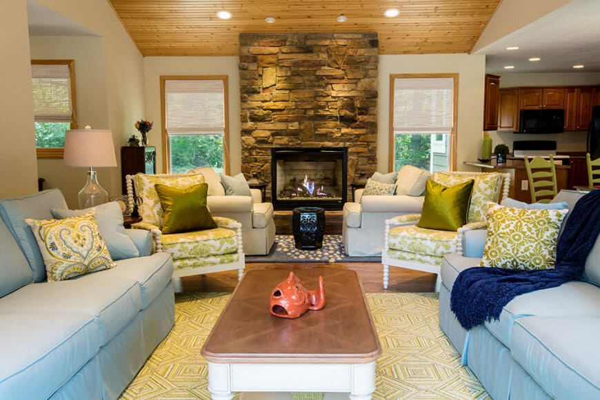 A coffee table sits in between facing sofas in this living room with green floral and gray skirted armchairs near the stone brick fireplace. It has wood plank ceiling and hardwood flooring topped by patterned rugs.