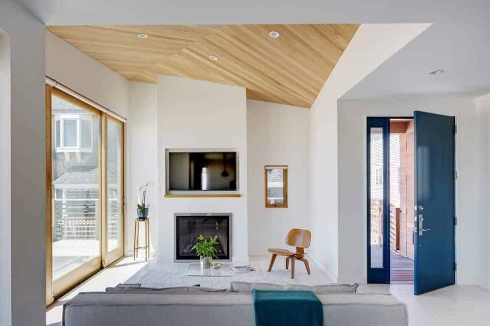 A blue door opens to this living room with a wooden chair and gray sofa paired with a glass coffee table. It includes a fireplace and TV fitted on the white pillar.