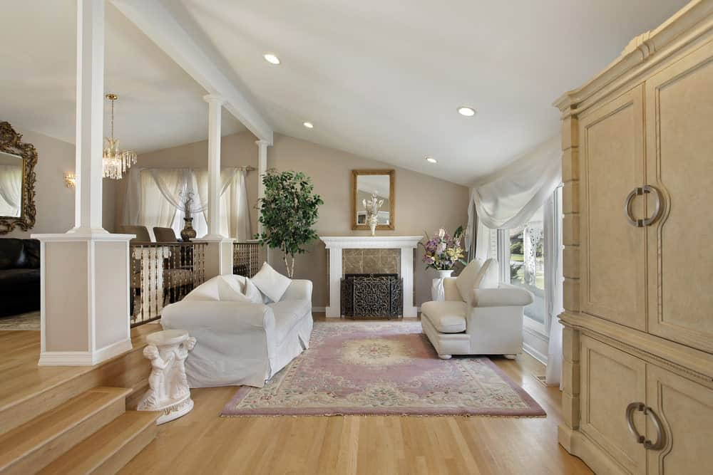 Cottage style living room offers white seats and a shabby chic rug that lays on the hardwood flooring. It includes a wooden framed mirror and a fireplace enclosed in an ornate three-panel screen.