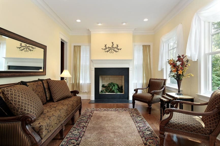 Patterned cushioned chairs match the pillows that lay on the floral printed sofa over the hardwood flooring. This room features a bordered area rug and a brick fireplace framed with black surround and white mantel.