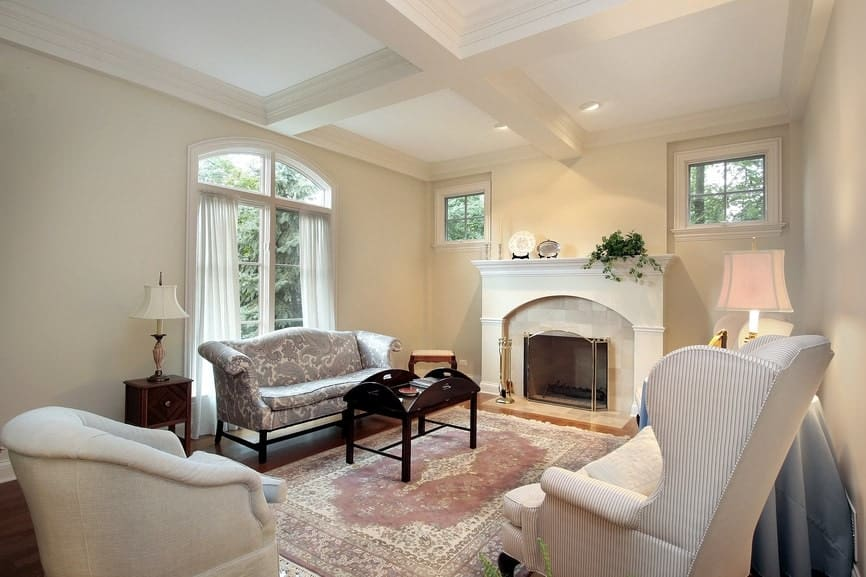 Cottage style living room with cozy seats and a dark wood coffee table that sits on a tasseled area rug. It includes a fireplace enclosed in a three-panel screen.