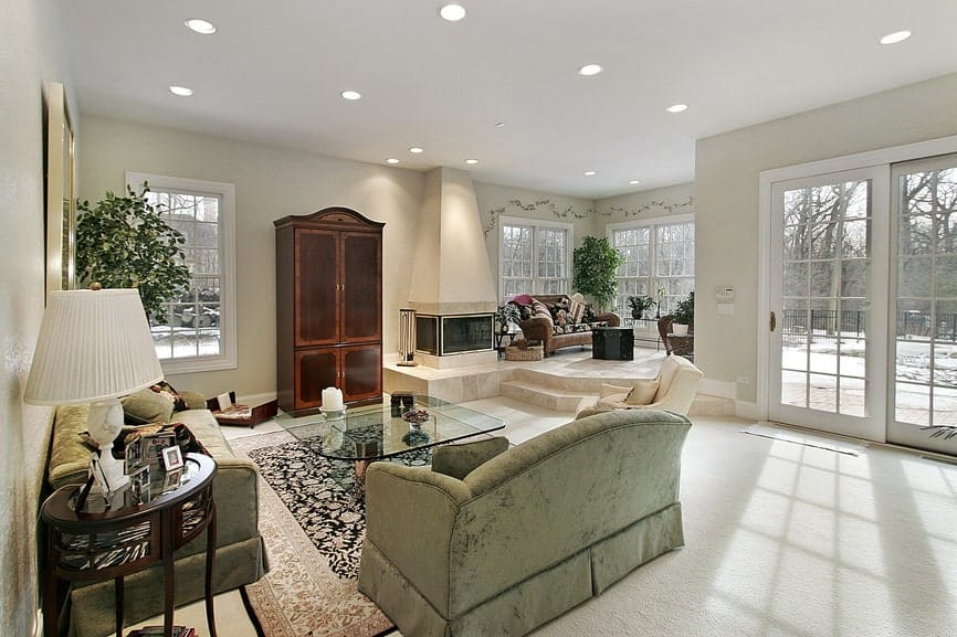 Large living room with multiple seating areas and a three-sided fireplace next to the wooden cabinet. It has carpet flooring and white framed windows overlooking the serene outdoor view.
