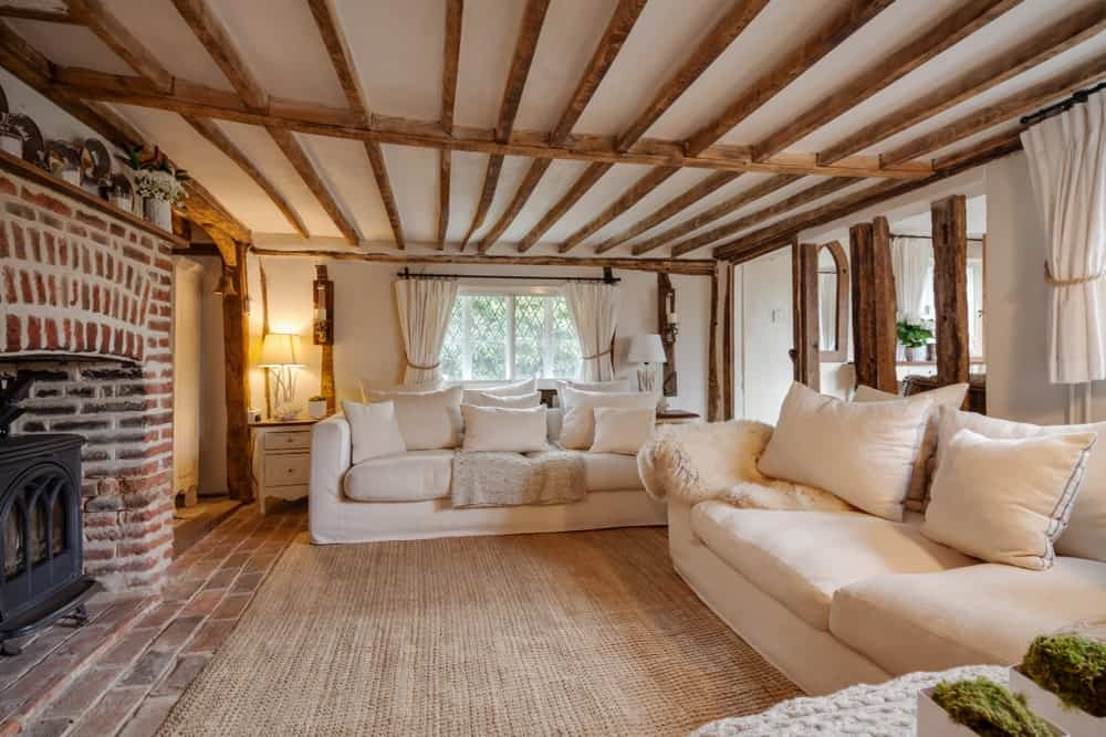 Cozy living room with wood beam ceiling and brick flooring topped by a jute area rug. It includes white sectional sofas and a freestanding fireplace against the red bricks.