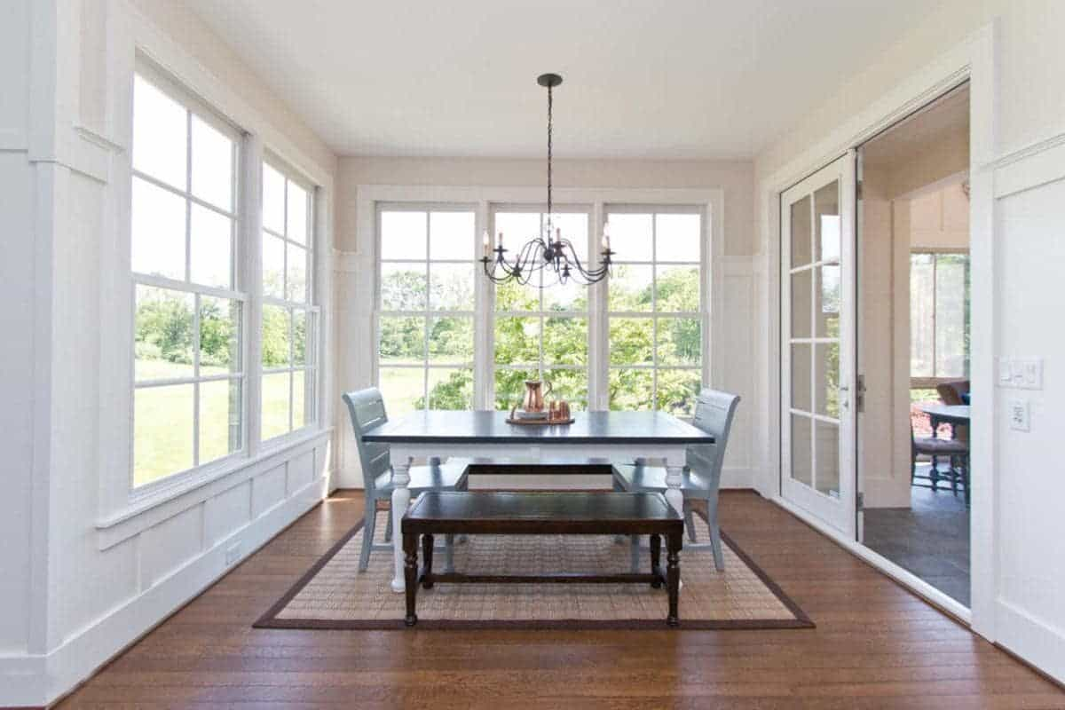 The highlight of this Farmhouse-style dining room is the lush green scenery outside the tall French windows that dominate the white walls contrasted by the dark hardwood flooring that pairs well with the wooden dining table and its wooden benches.