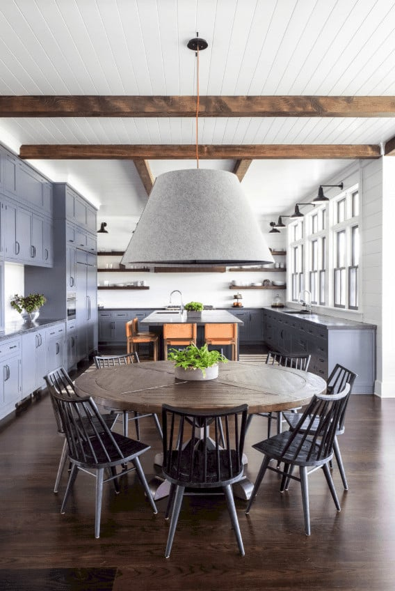 The large bell-like hood of the pendant light is almost as big as the round wooden dining table paired with black wooden dining chairs. This informal dining area is within the walls of the kitchen that provides a nice gray background.