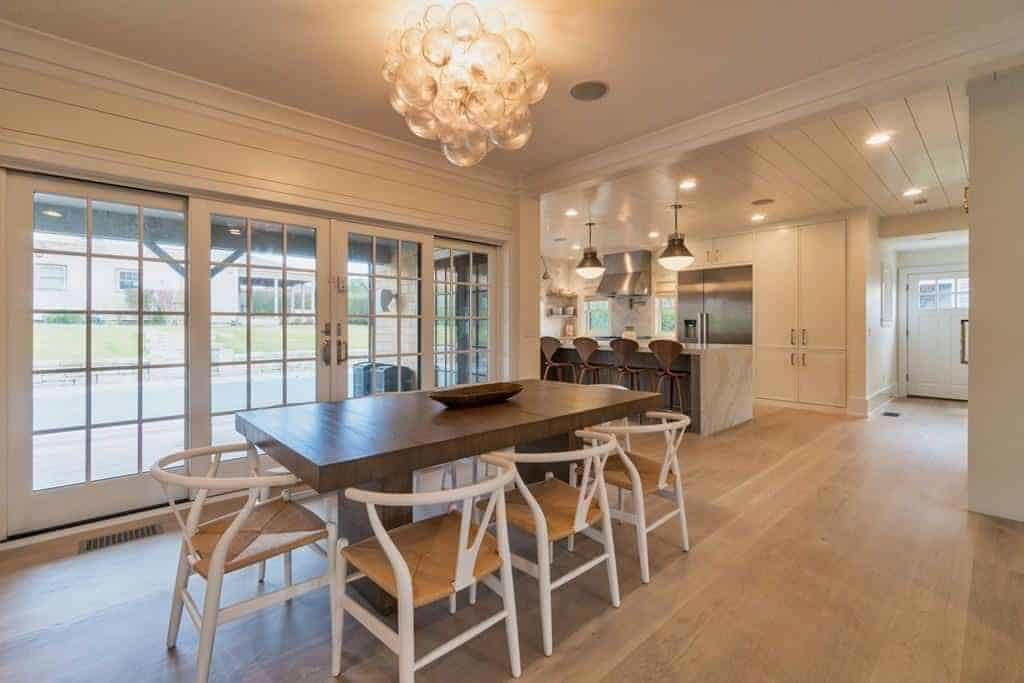 This Farmhouse-style dining room has white wooden wishbone chairs with rustic woven wicker seats that complement the hardwood flooring and the rectangular wooden dining table that has a slightly darker brown hue warmed by the yellow lights of the decorative lighting above.