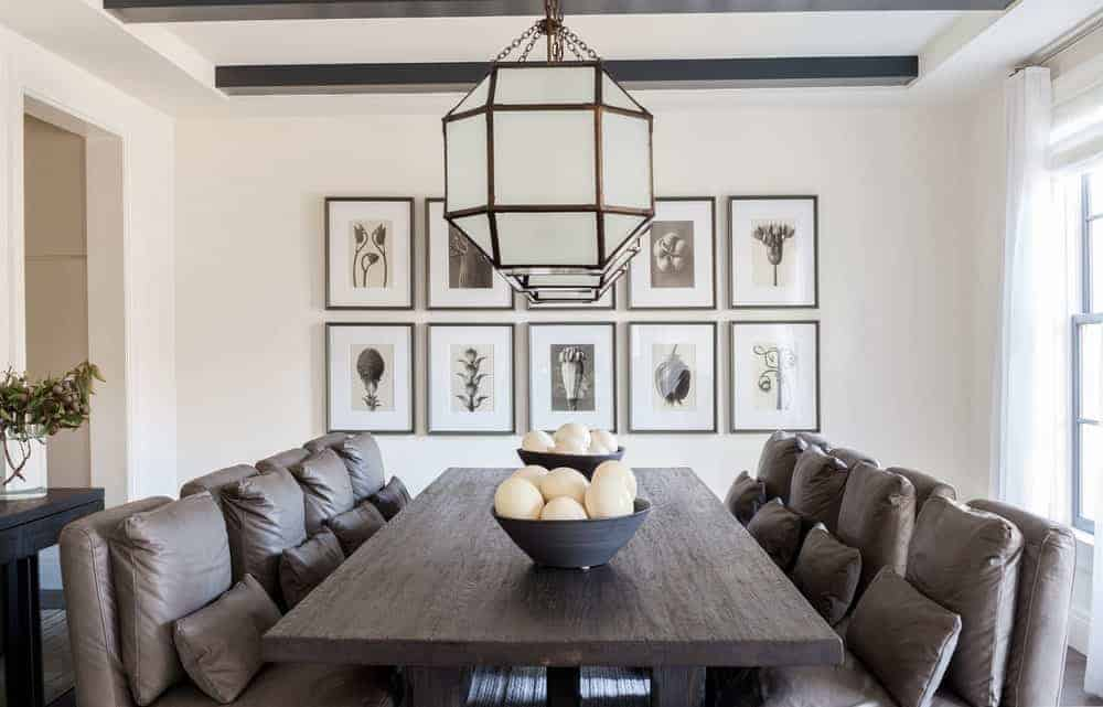 This is a Farmhouse-style dining room with comfortable dining chairs that have brown leather cushions and <a class=