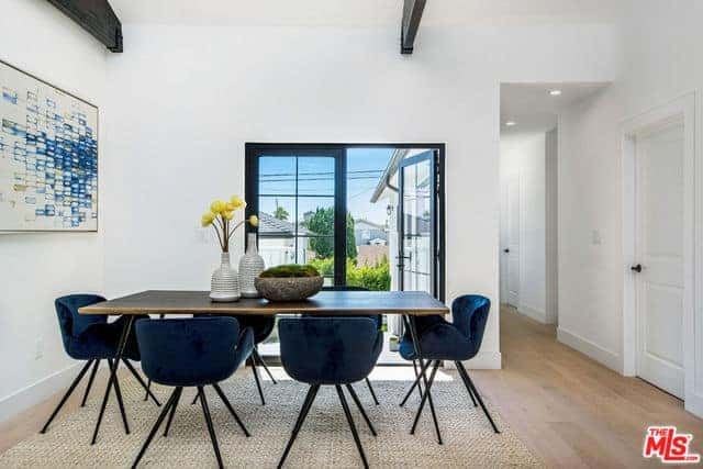 The blue velvet cushioned chairs are the highlights of this simple Farmhouse-style dining room. It matches with the colorful abstract painting mounted on the white wall by the head of the wooden dining table that complements the hardwood flooring.