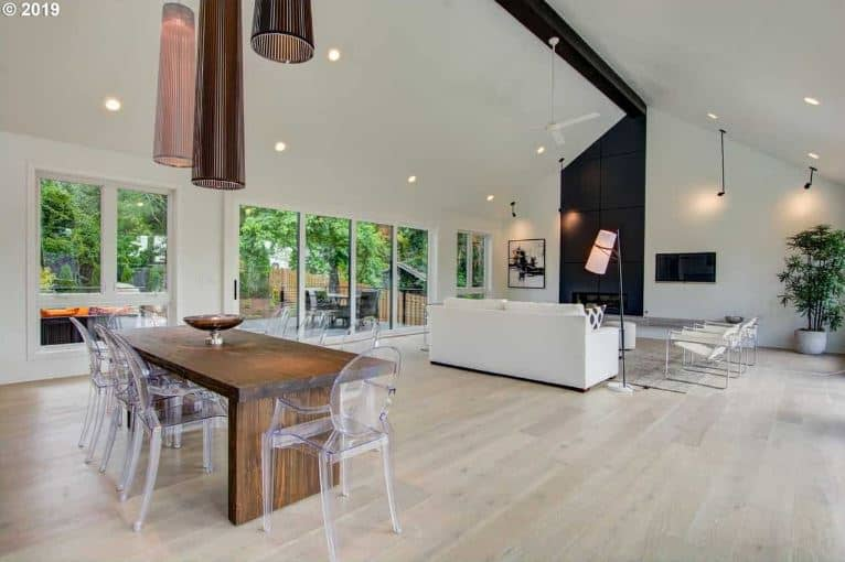 This simple dining area is part of a great room that also houses the living room area on the same light hardwood flooring that makes the wooden dining table stand out. This is complemented by its modern see through dining chairs.
