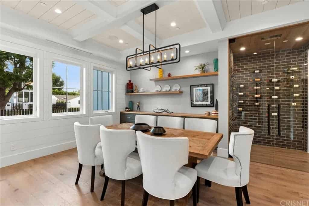 This dining room has white cushioned wing back chairs that stand out against the wooden dining table that blends with the hardwood flooring topped with a white ceiling with exposed beams supporting a Farmhouse-style chandelier.