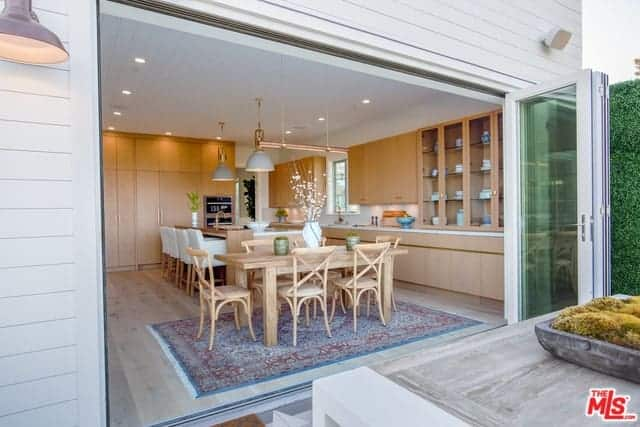 This is an informal Farmhouse-style dining area by the kitchen. The rustic wooden dining set is bathed in natural lights coming from the entire wall opening up courtesy of the folding glass doors with green tint and white frames that match the white ceiling.