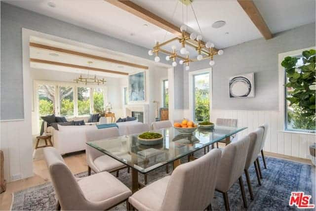 The glass-top dining table is paired with light gray cushioned dining chairs that stand out against the blue patterned area rug underneath. This dining room has a white ceiling with exposed wooden beams and a golden modern chandelier.