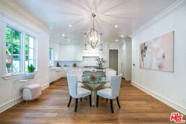 This small dining area has a stainless steel spherical decorative lighting hanging over the round glass-top dining table and its white cushioned wing-back chairs that stand out against the hardwood flooring but blends with the white walls.