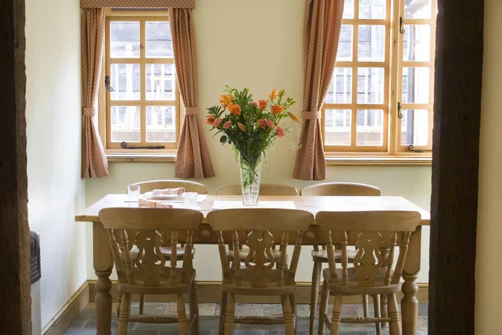 The charming wooden dining table has a simple design to its wooden legs that match with the designs and finish of the wooden dining chairs. This setup is given a nice background of brilliant windows with pink patterned curtains.