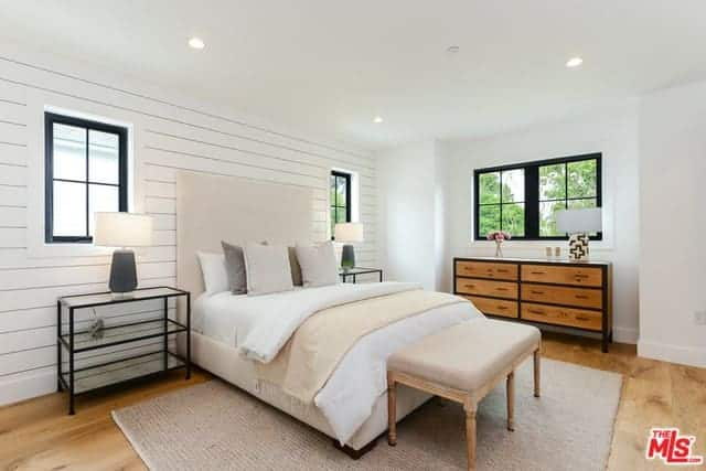 This is a simple and bright Farmhouse-style bedroom with white walls and white ceiling with recessed lights. These are further lightened by the natural lights coming in from the windows flanking the beige cushioned bed with white sheets.